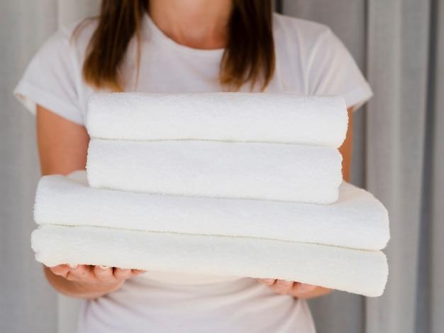 La donna del primo piano che tiene il bianco ha piegato gli asciugamani puliti