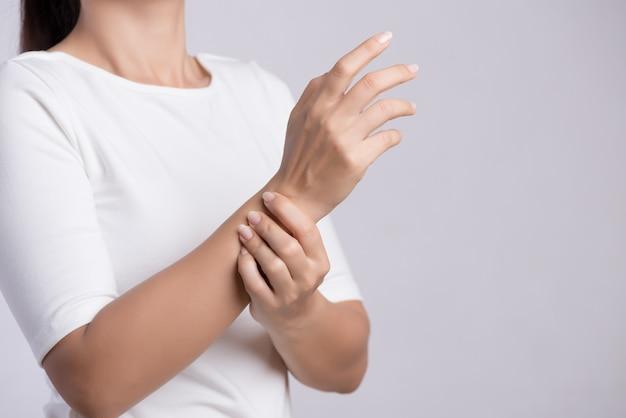 La donna del primo piano tiene la sua ferita della mano del polso, ritenente dolore. concetto di assistenza sanitaria.
