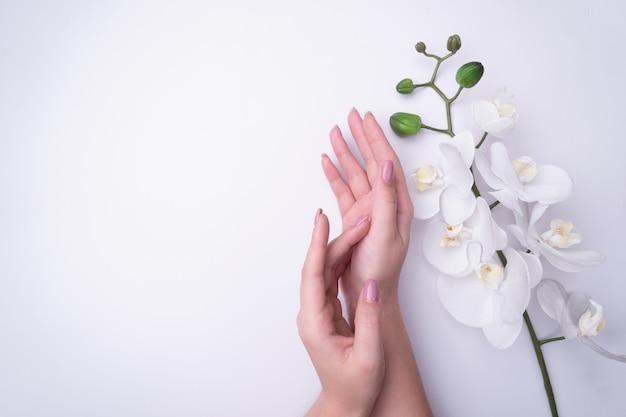 La donna del ritratto di fashionrt fiorisce in sua mano con un trucco contrastante luminoso.