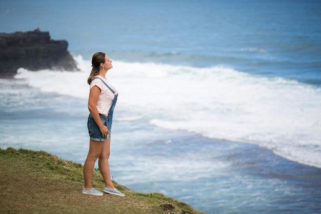 La donna del viaggiatore di libertà in cima alla montagna e gode della bella vista sul mare. mauritius