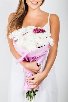 La donna delicata del primo piano passa la tenuta del mazzo di fiori