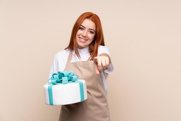 La donna dell'adolescente della testarossa con una grande torta sopra la parete isolata indica il dito voi con un'espressione sicura