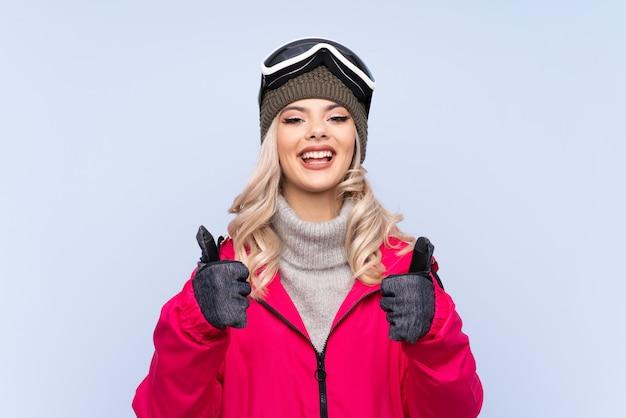 La donna dell'adolescente dello sciatore con i vetri di snowboard che dà un pollice in su gesto