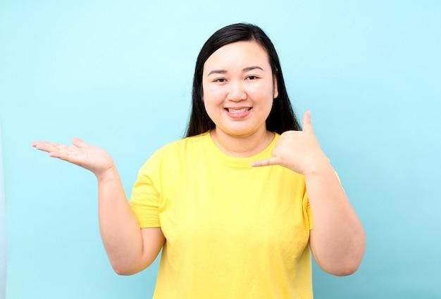 La donna dell'asia del ritratto sta fingendo di rispondere al telefono per invitare, isolata su fondo blu in studio.