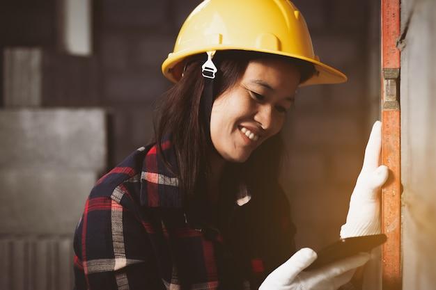 La donna dell'asia, l'ingegnere che usando lo smartphone che lavora al sito funziona felice.