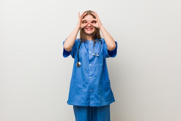 La donna dell'infermiera dei giovani contro una parete bianca che mostra bene firma sopra gli occhi
