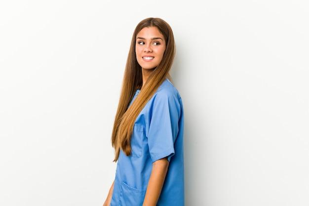 La donna dell'infermiera dei giovani osserva da parte sorridente, allegro e piacevole