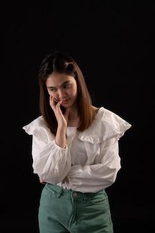 La donna della depressione che sta seria sulla siluetta asiatica triste triste della donna nello scuro.