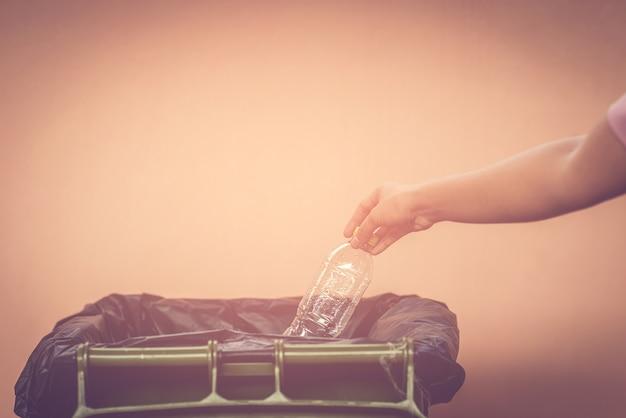 La donna della mano ha messo la bottiglia di plastica o la spazzatura nella spazzatura con lo sfondo arancione.