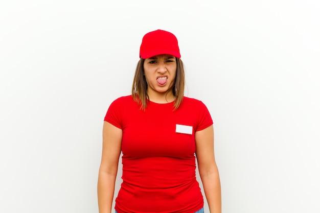 La donna delle consegne si sente disgustata e irritata, sporge la lingua, non ama qualcosa di brutto e schifoso contro il bianco