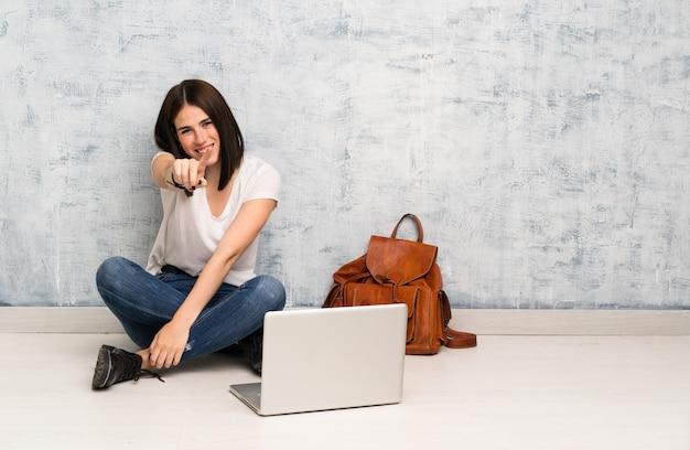La donna dello studente che si siede sul pavimento indica il dito con un'espressione sicura
