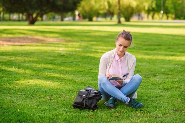 La donna dello studente sta studiando all'aperto nel campus universitario al tramonto.