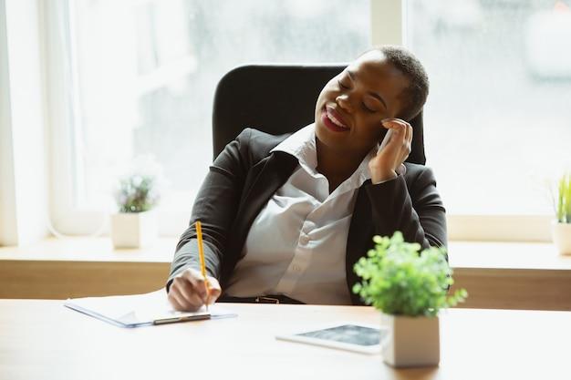 La donna di affari afroamericana in abbigliamento dell'ufficio che sorride, sembra sicura e felice, occupata