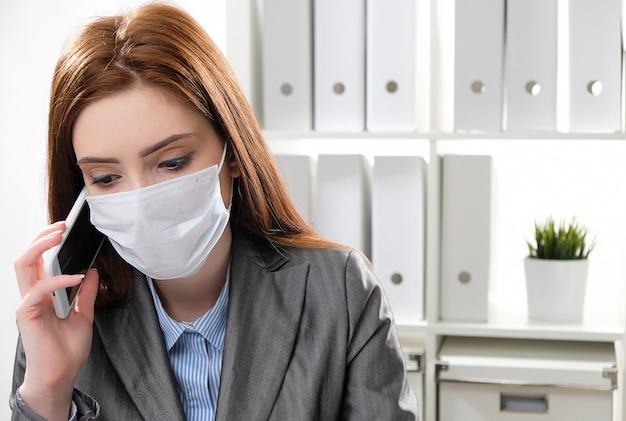 La donna di affari ammalata in una mascherina medica protettiva all'ufficio utilizza un telefono cellulare