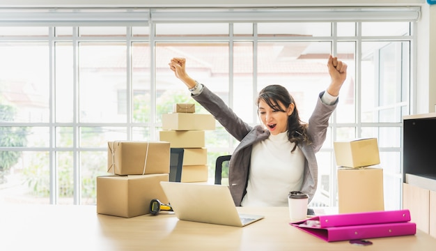 La donna di affari arma su con il computer portatile e la scatola di cartone