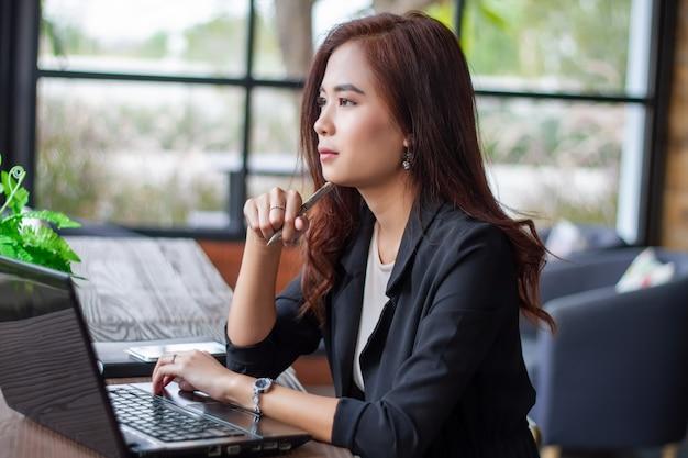 La donna di affari asiatica sta pensando di creare nuovi posti di lavoro e sta sorridendo e lavorando felice