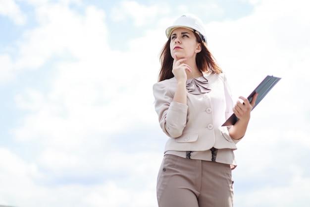 La donna di affari attraente nel vestito beige sta sul tetto e tiene la compressa