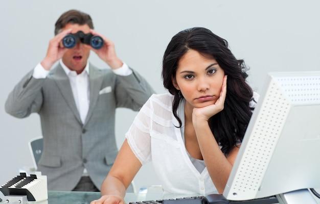 La donna di affari castana si è infastidita da un uomo che guarda tramite il binocolo