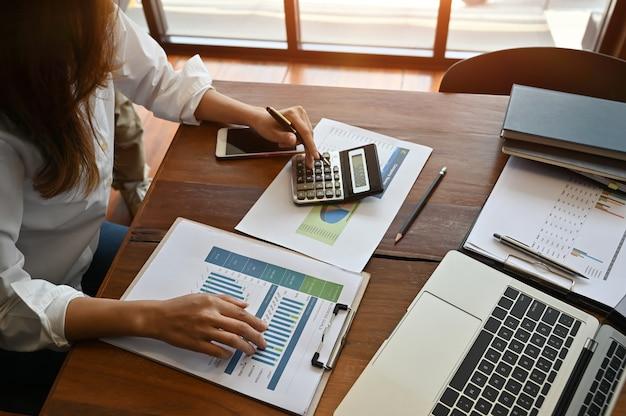 La donna di affari che lavora con i dati di finanza e calcola l'investimento.