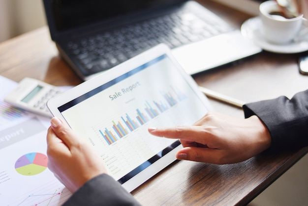 La donna di affari che lavora nell'ufficio con il rapporto di affari di controllo facendo uso del computer portatile di tecnologie informatiche della compressa con il calcolatore e la tazza di caffè / vendita riferisce i soldi che analizzano il grafico dei grafici