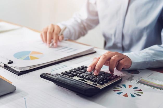 La donna di affari che lavora nella finanza e nella contabilità analizza il bilancio finanziario nell'ufficio