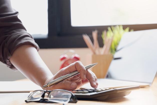 La donna di affari che per mezzo del calcolatore e del computer portatile per fa le finanze matematiche