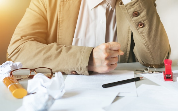 La donna di affari che si siede con la testa in mani allo scrittorio ha coperto le carte sgualcite. imprenditore che non sa cosa fare dopo con la sua attività. concetto di delusione, perdita di attività