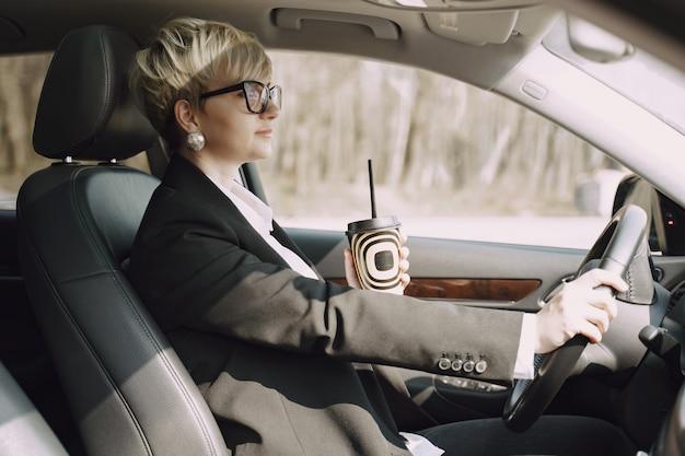 La donna di affari che si siede dentro un'automobile e beve un caffè