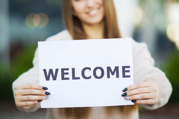 La donna di affari con capelli lunghi che tengono un cartello il bordo con un benvenuto ha fondo dell'aeroporto