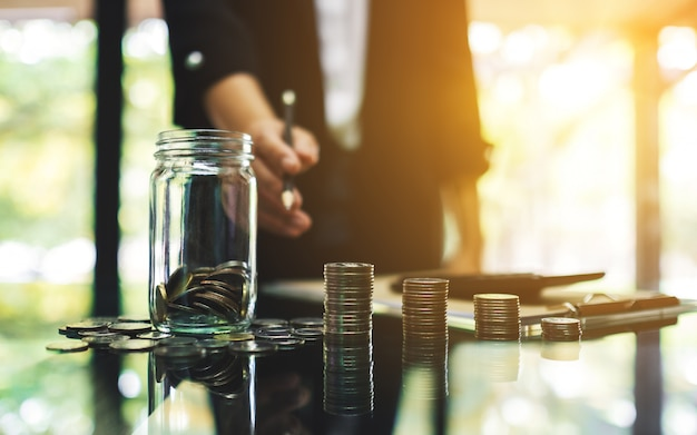 La donna di affari con le monete impila, un barattolo di vetro dei soldi e un calcolatore sulla tavola per il risparmio e il concetto finanziario