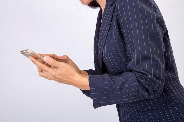 La donna di affari controlla i suoi email sul suo smartphone del dispositivo del telefono cellulare