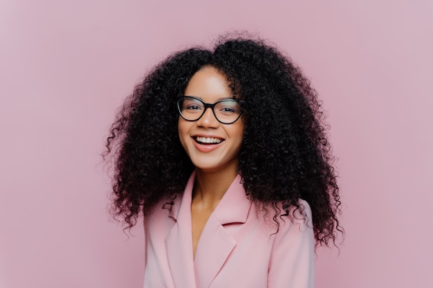 La donna di affari dai capelli riccia positiva indossa gli occhiali