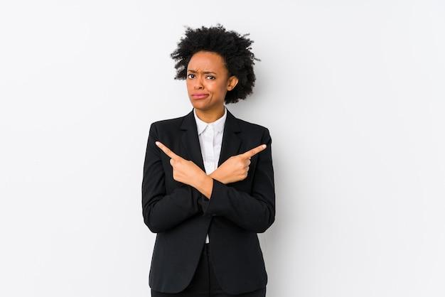 La donna di affari dell'afroamericano di mezza età contro una parete bianca ha isolato i punti lateralmente, sta provando a scegliere tra due opzioni.