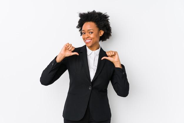 La donna di affari dell'afroamericano di mezza età contro una parete bianca si sente orgogliosa e sicura di sé, esempio da seguire.