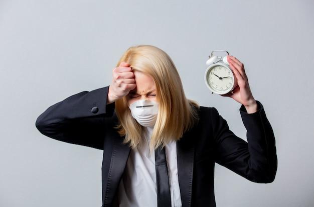 La donna di affari disperata in vestito nero e maschera facciale tiene la sveglia