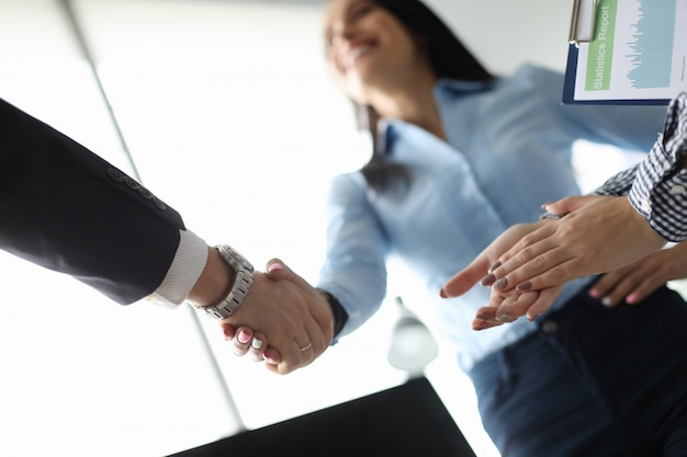 La donna di affari e l'uomo d'affari stringono la mano in ofiice