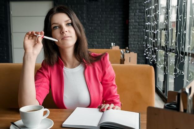 La donna di affari è seduta in un caffè a pensare a qualcosa