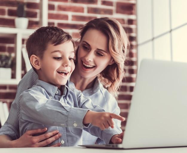 La donna di affari e suo figlio piccolo sveglio stanno usando un computer portatile.