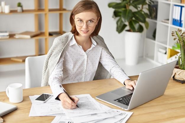 La donna di affari elegante si è vestita formalmente che si siede con il computer portatile