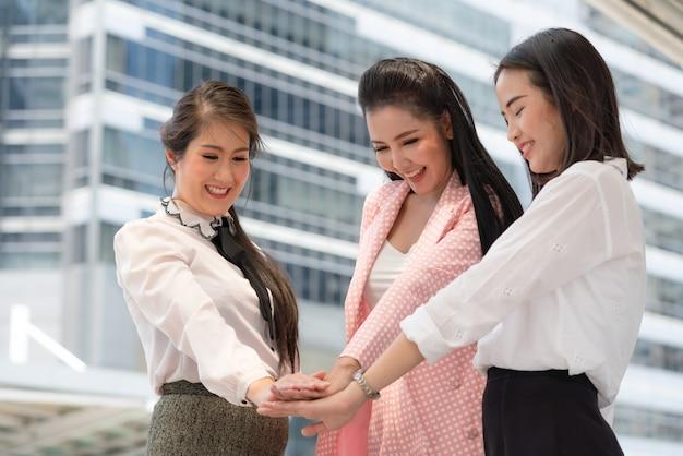 La donna di affari felicemente asiatica unisce le mani insieme per funzionare il successo