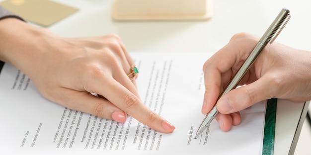 La donna di affari firma il contratto di accordo in ufficio.