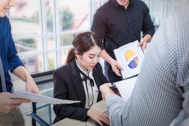La donna di affari firma un documento e una riunione con lavoro di squadra di affari.