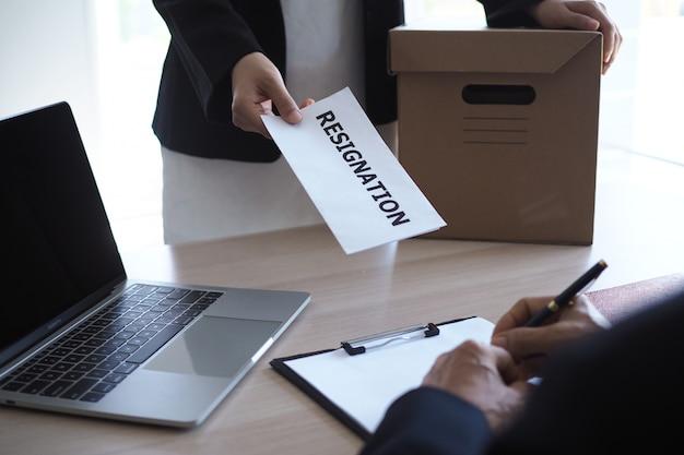 La donna di affari ha scatole per uso personale e sta inviando le lettere di dimissioni ai quadri