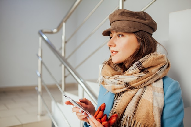 La donna di affari in cappotto si leva in piedi sulle scale nel centro commerciale con lo smartphone. shopping. moda