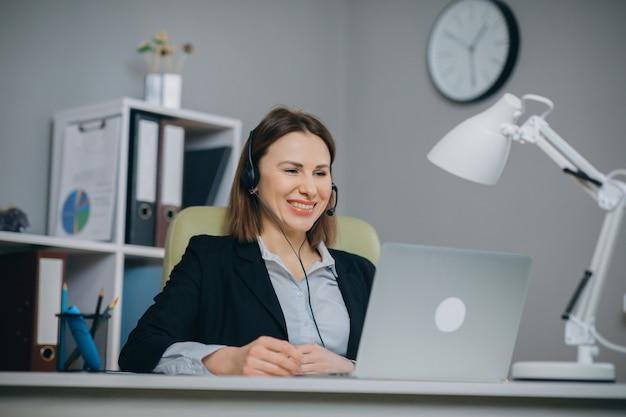 La donna di affari in cuffie che tiene la conversazione del rapporto finanziario di carta alla webcam fa la video chiamata in ufficio