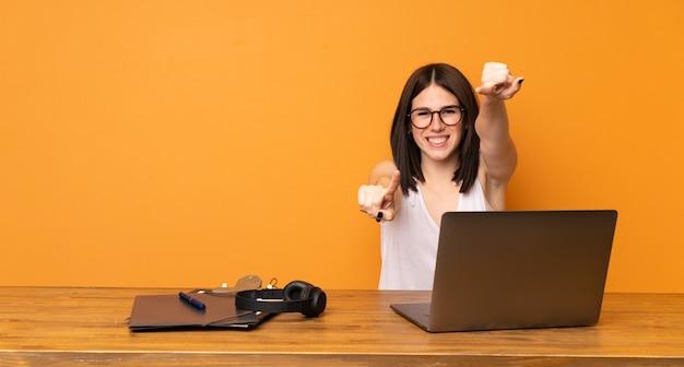 La donna di affari in un ufficio indica il dito mentre sorride