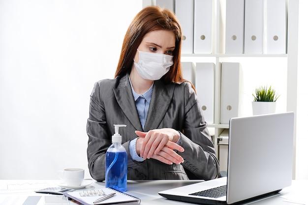La donna di affari in una mascherina medica si disinfetta le mani con un agente antibatterico a base di alcol