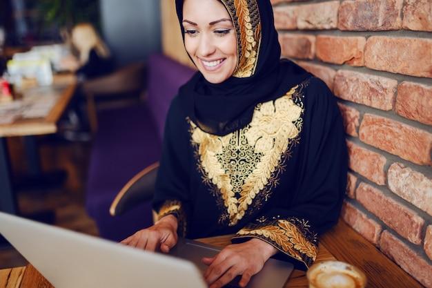 La donna di affari musulmana sbalorditiva si è vestita nell'usura tradizionale che si siede nel caffè e che utilizza il computer portatile. sulla scrivania sono laptop e caffè.