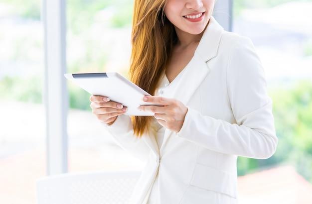 La donna di affari nel bianco sta usando la compressa in ufficio