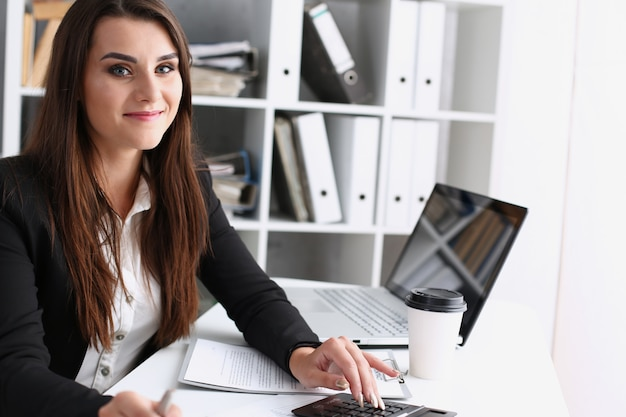 La donna di affari nell'ufficio tiene la sua mano sulla calcolatrice